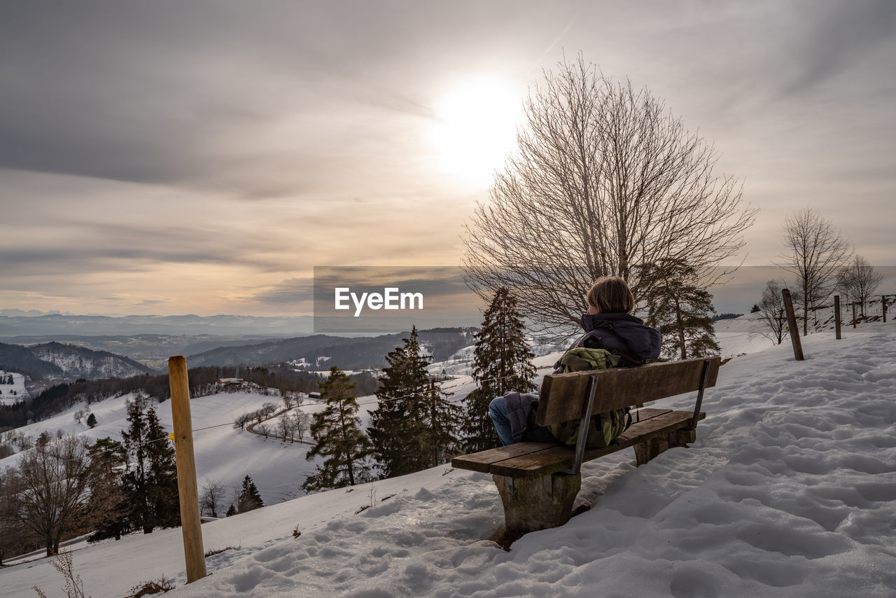 Woman sitting on bench over snow covered land against sky