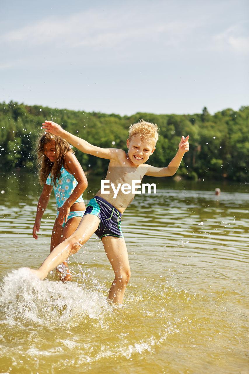 Siblings playing in lake against sky
