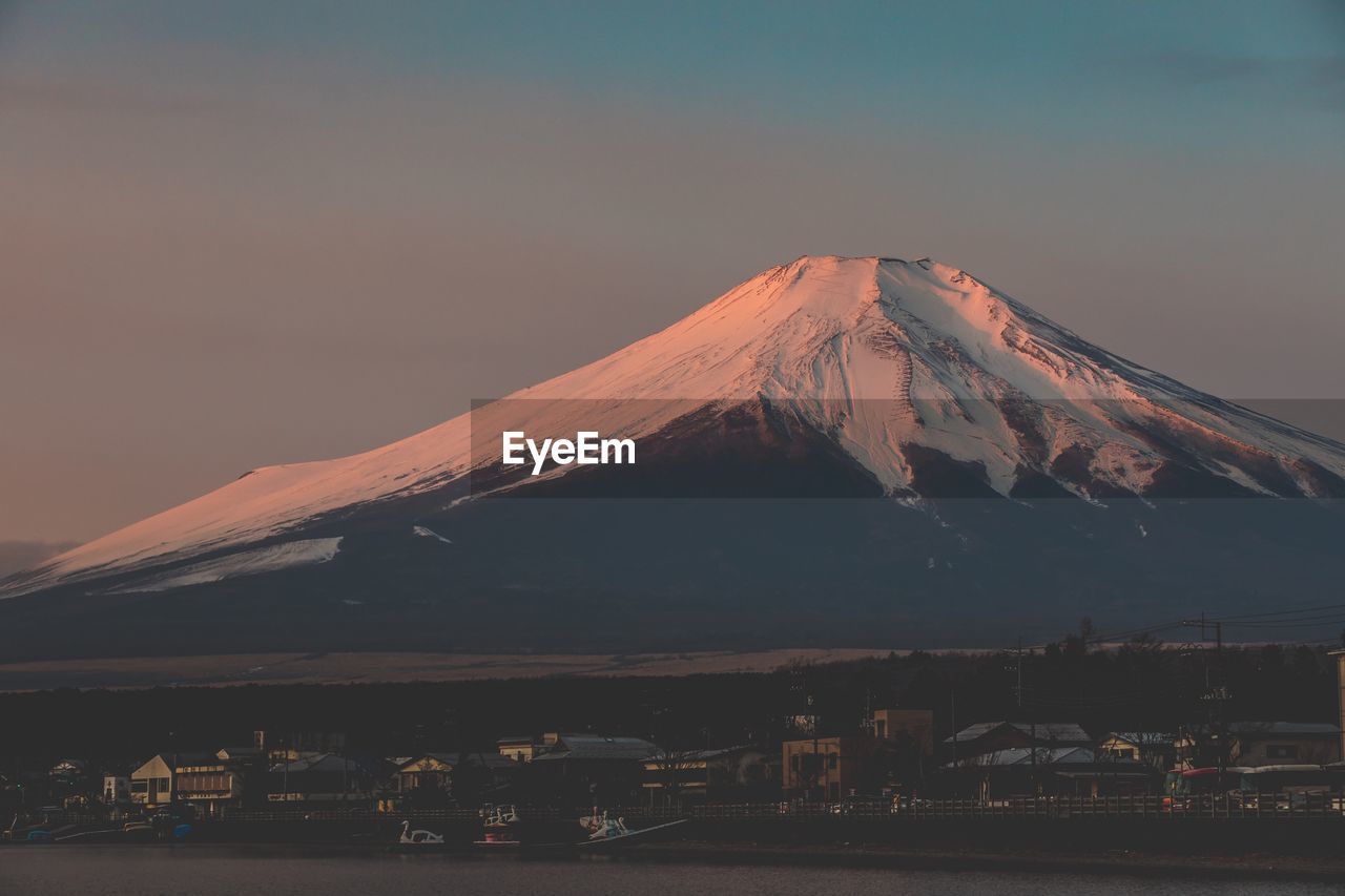 mountain, sky, scenics - nature, beauty in nature, volcano, architecture, nature, no people, built structure, cold temperature, building exterior, environment, snow, landscape, sunset, snowcapped mountain, tranquil scene, outdoors, winter, mountain peak