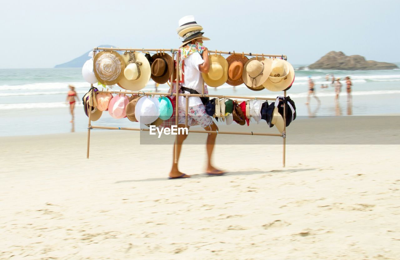 Full Length Of Man Selling Hats At Beach