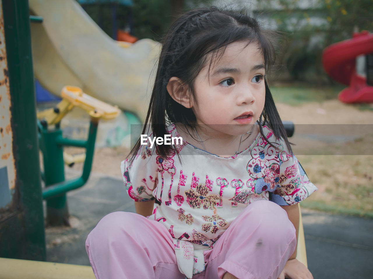 Cute girl looking away while sitting at playground