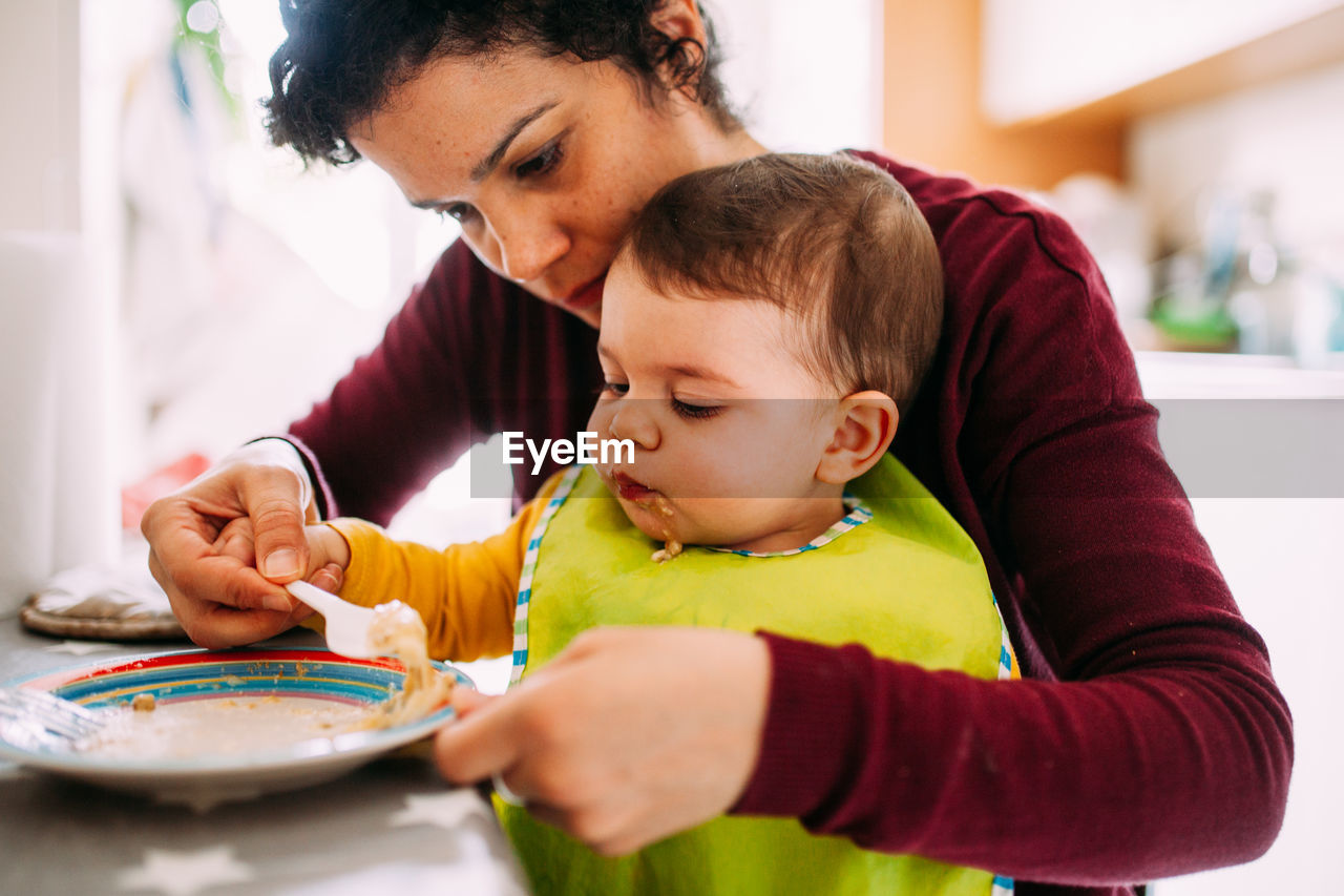 childhood, child, family, parent, real people, bonding, family with one child, togetherness, indoors, innocence, females, love, domestic life, lifestyles, holding, men, headshot, daughter, positive emotion