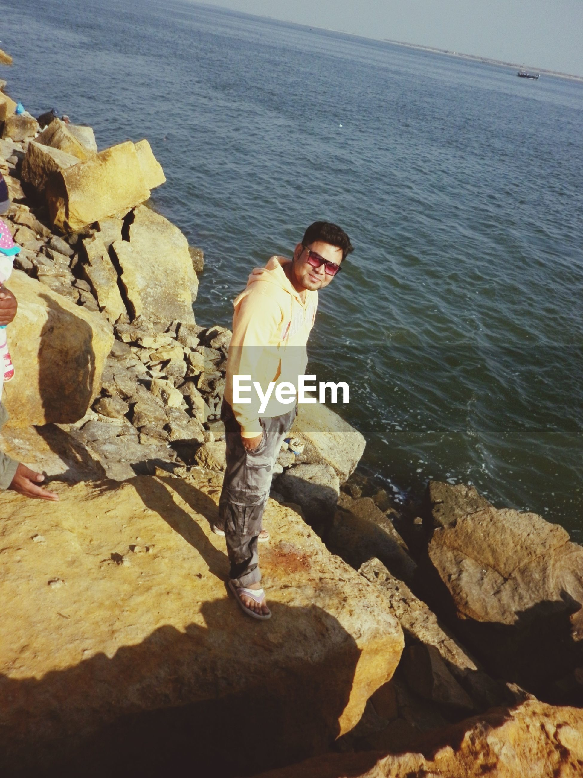 lifestyles, water, leisure activity, rock - object, full length, sea, standing, casual clothing, nature, vacations, rock, outdoors, young adult, rock formation, person, sunlight, shore, high angle view