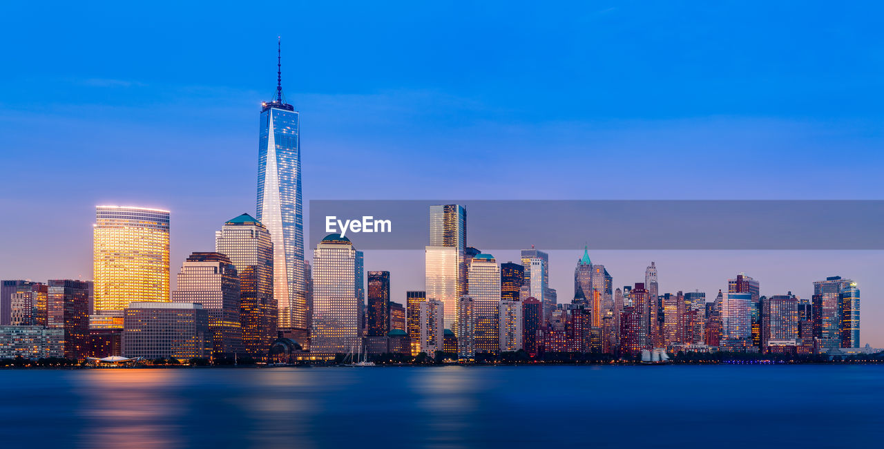 Illuminated Lower Manhattan Buildings By Hudson River