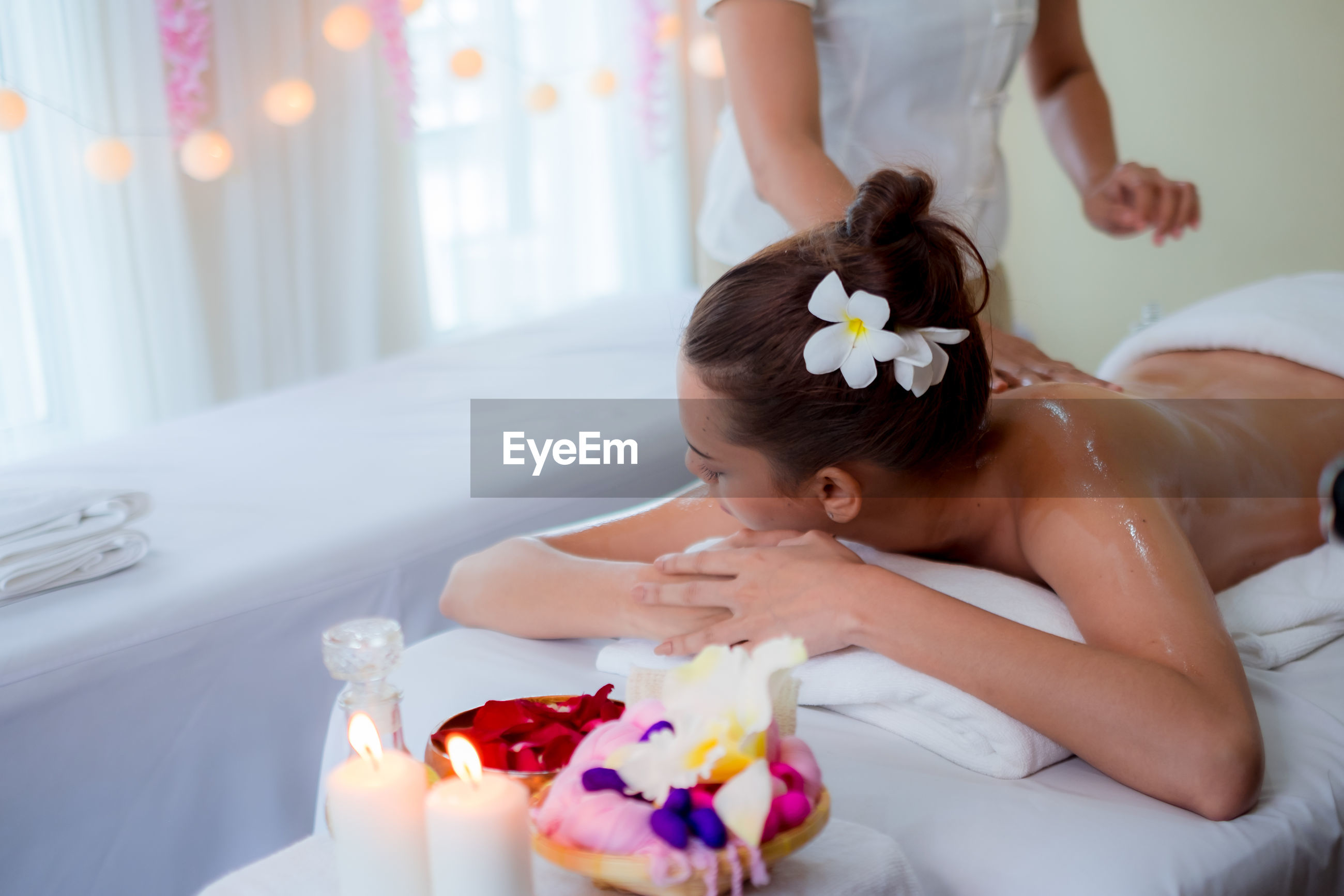 Young woman lying on bed at beauty spa