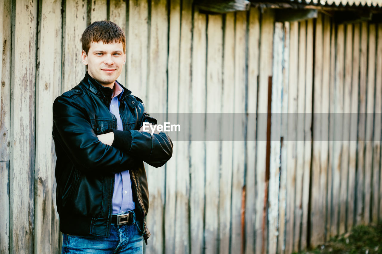 Portrait Of Man Smiling While Standing By Wooden Wall