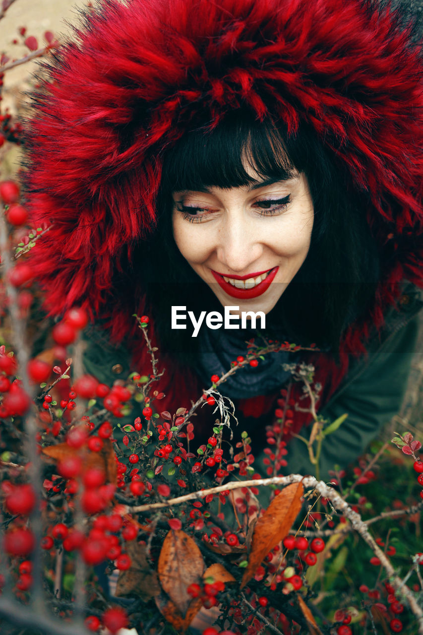 High Angle View Of Woman Wearing Warm Clothing Amidst Red Berries On Plants