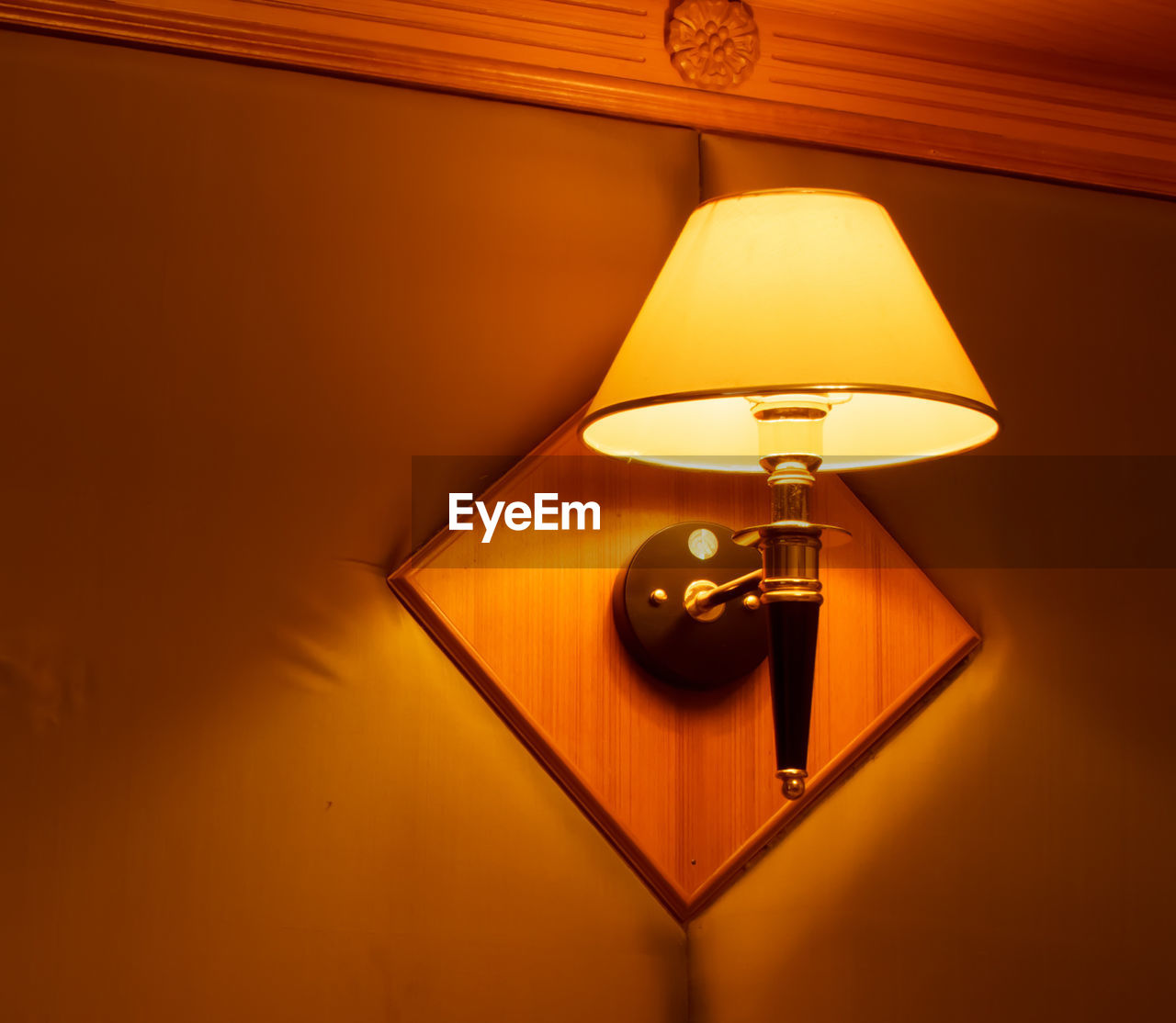 lighting equipment, illuminated, electric lamp, electricity, indoors, glowing, light, no people, electric light, lamp shade, technology, table, wall - building feature, light - natural phenomenon, close-up, orange color, pendant light, wood - material, retro styled, design, dark, ceiling