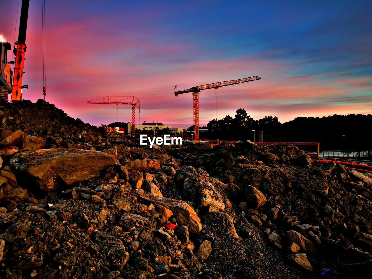 sky, sunset, rock, rock - object, solid, nature, crane - construction machinery, machinery, construction industry, industry, cloud - sky, construction site, no people, orange color, construction machinery, land, development, architecture, fuel and power generation, outdoors, industrial equipment, construction equipment, pollution
