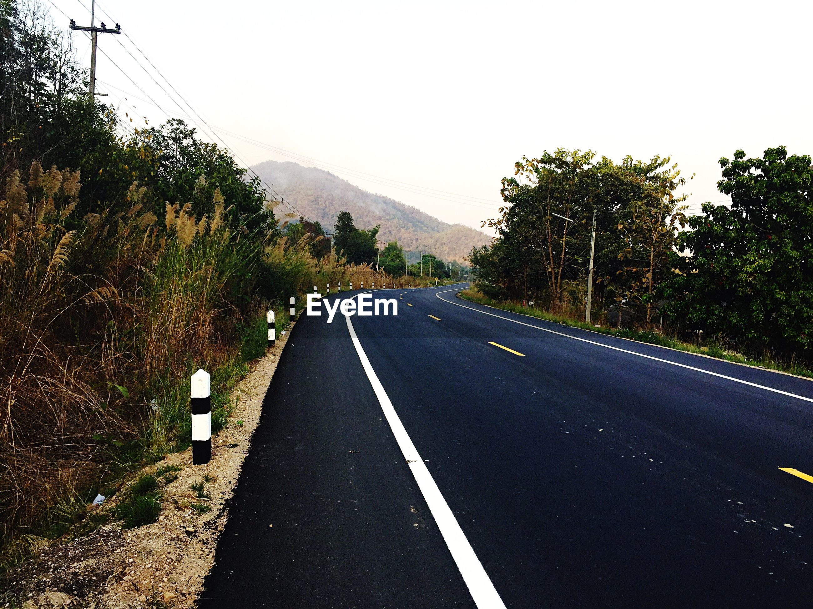 the way forward, transportation, road, road marking, diminishing perspective, vanishing point, tree, asphalt, country road, clear sky, mountain, empty road, sky, double yellow line, dividing line, street, empty, road sign, tranquility, nature