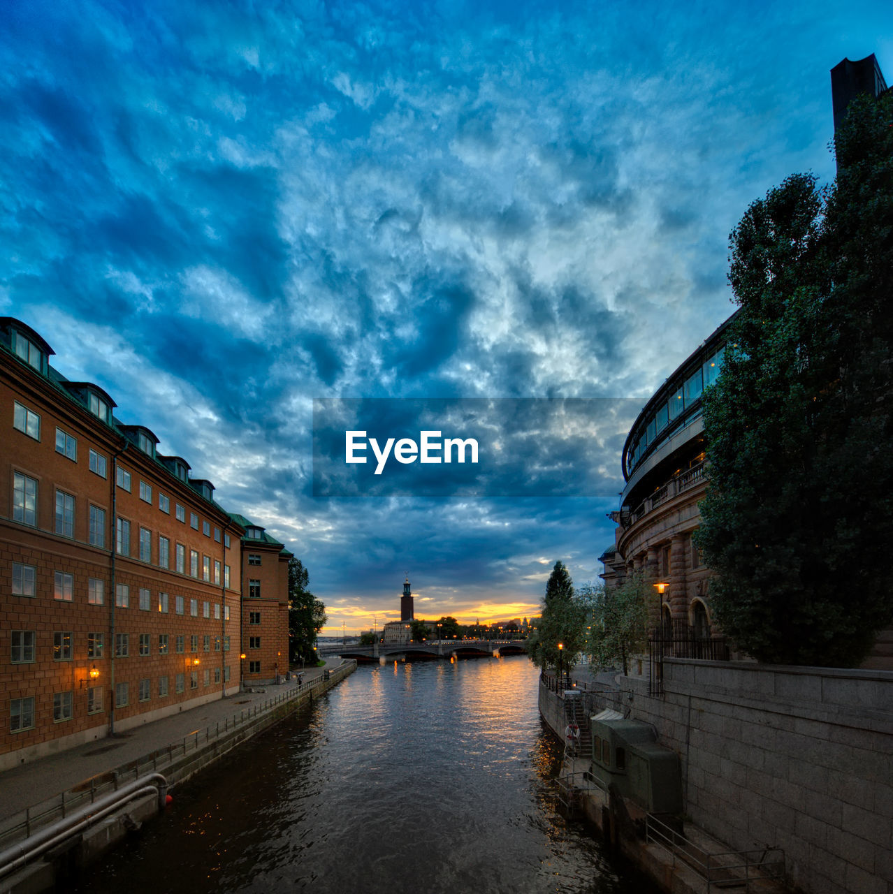 Canal Amidst Buildings In City At Sunset