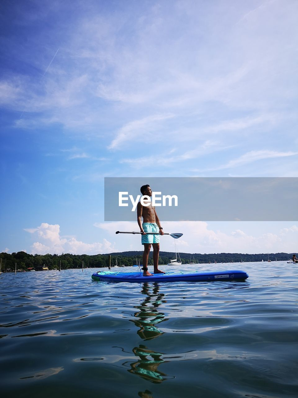 Shirtless Teenage Boy Paddleboarding In Sea Against Sky