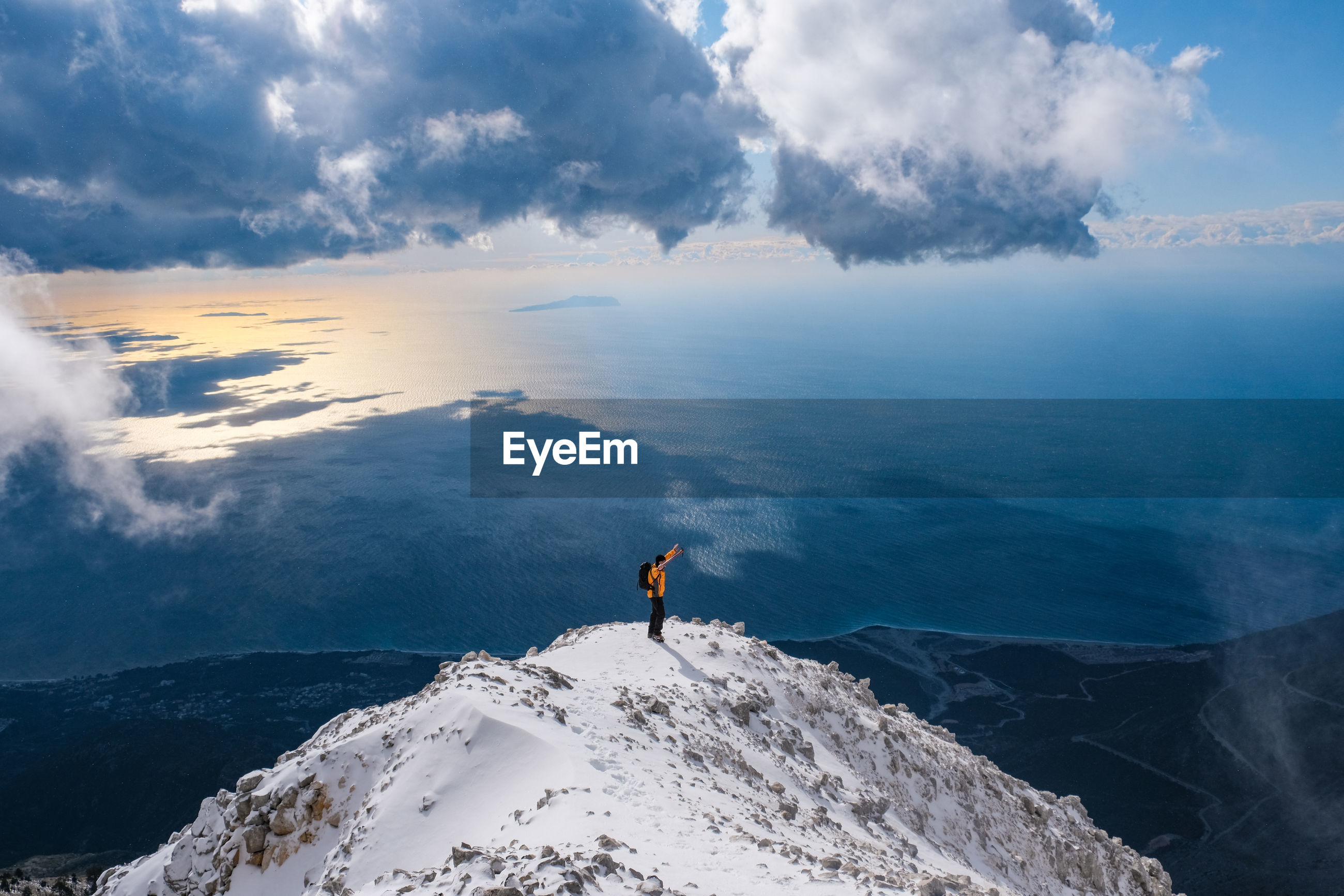 Man looking at sea by snowcapped mountain against sky