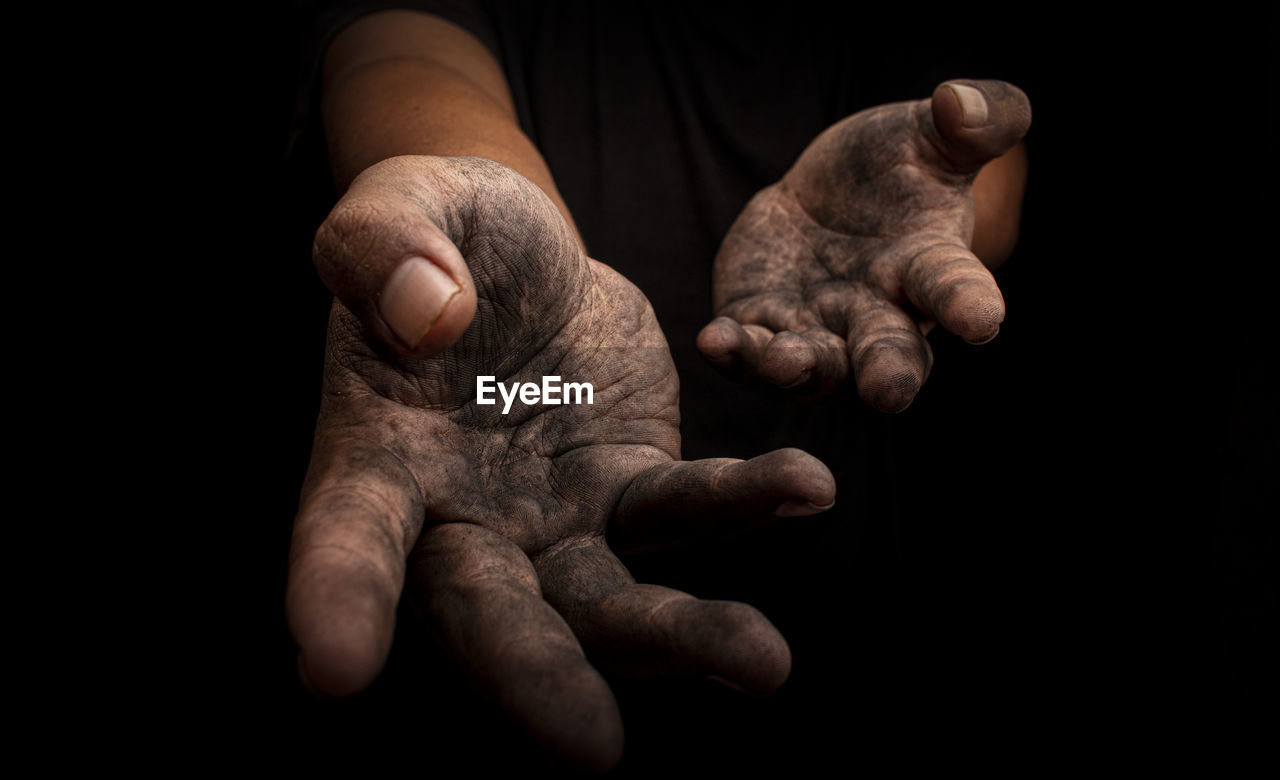 Close-up of messy hands gesturing against black background