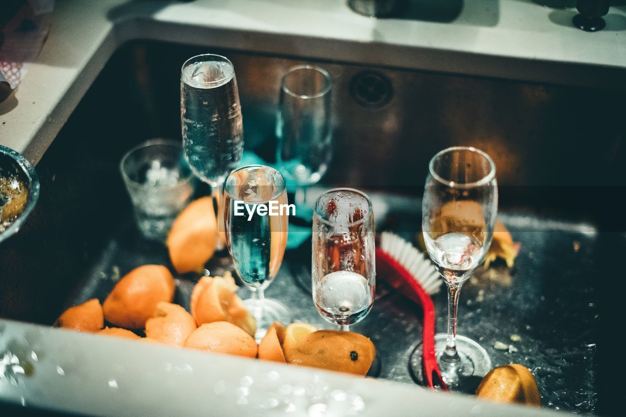 Close-Up Of Champagne Flutes And Lemon Slices In Sink