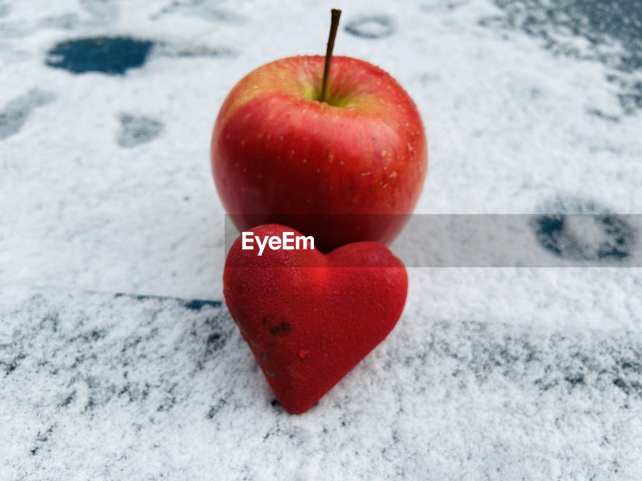 CLOSE-UP OF RED APPLE ON HEART SHAPE IN WINTER