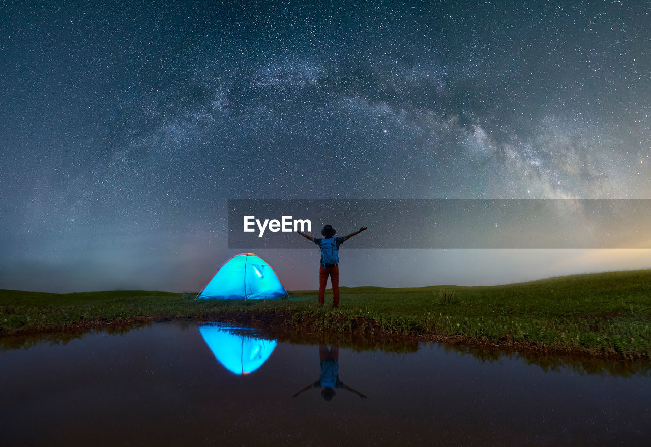 Rear View Of Mature Man With Arms Outstretched Standing On Grassy Field By Lake At Campsite Against Star Field