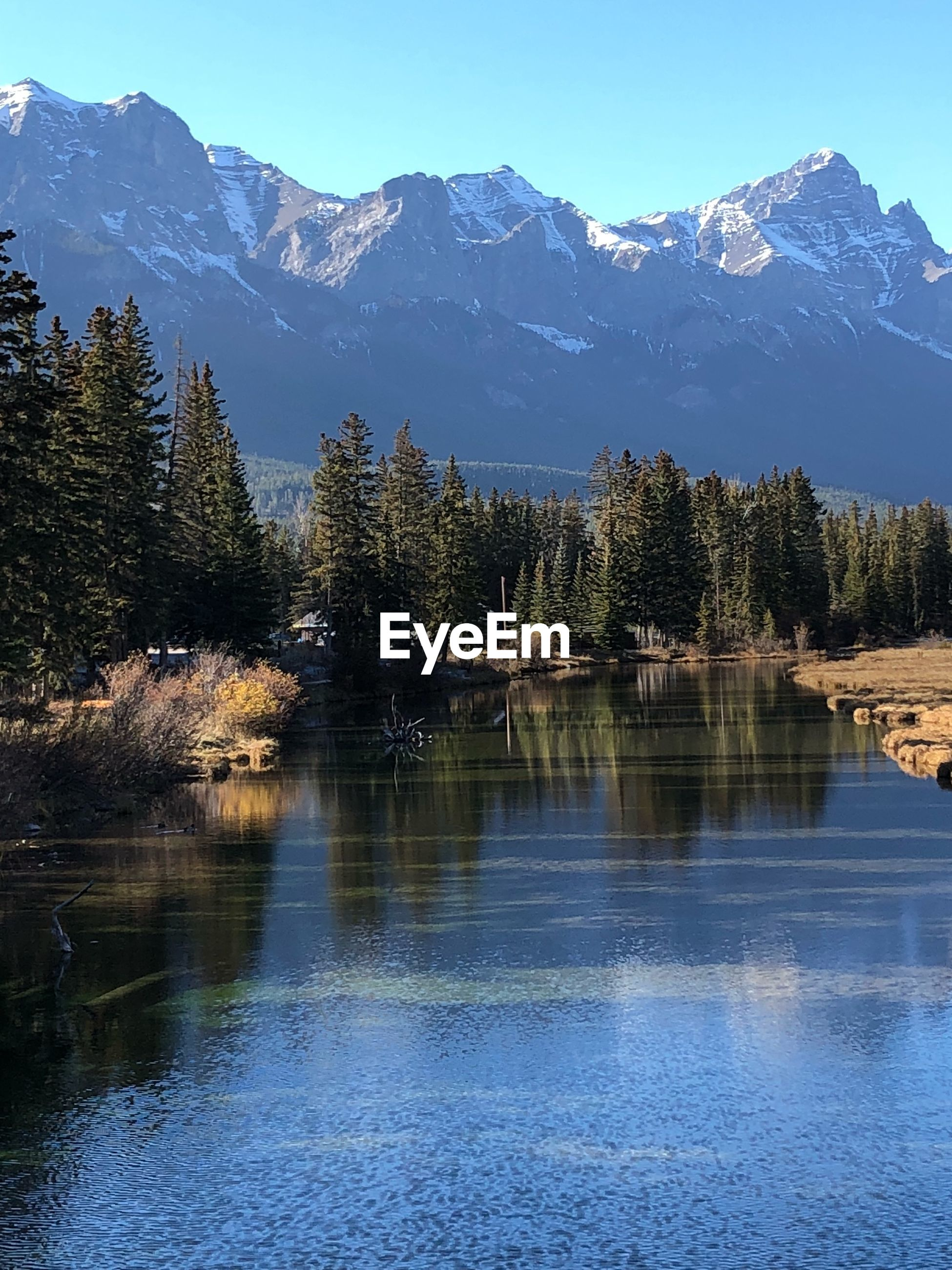 SCENIC VIEW OF LAKE BY MOUNTAINS AGAINST SKY DURING WINTER