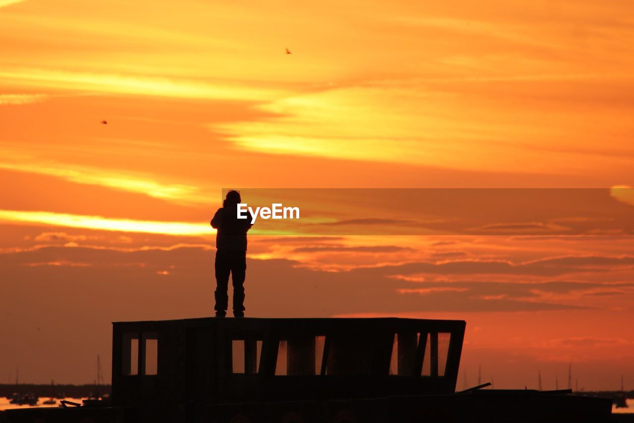 sunset, silhouette, orange color, sky, standing, one person, cloud - sky, beauty in nature, nature, real people, men, scenics - nature, full length, lifestyles, leisure activity, architecture, built structure, idyllic, outdoors