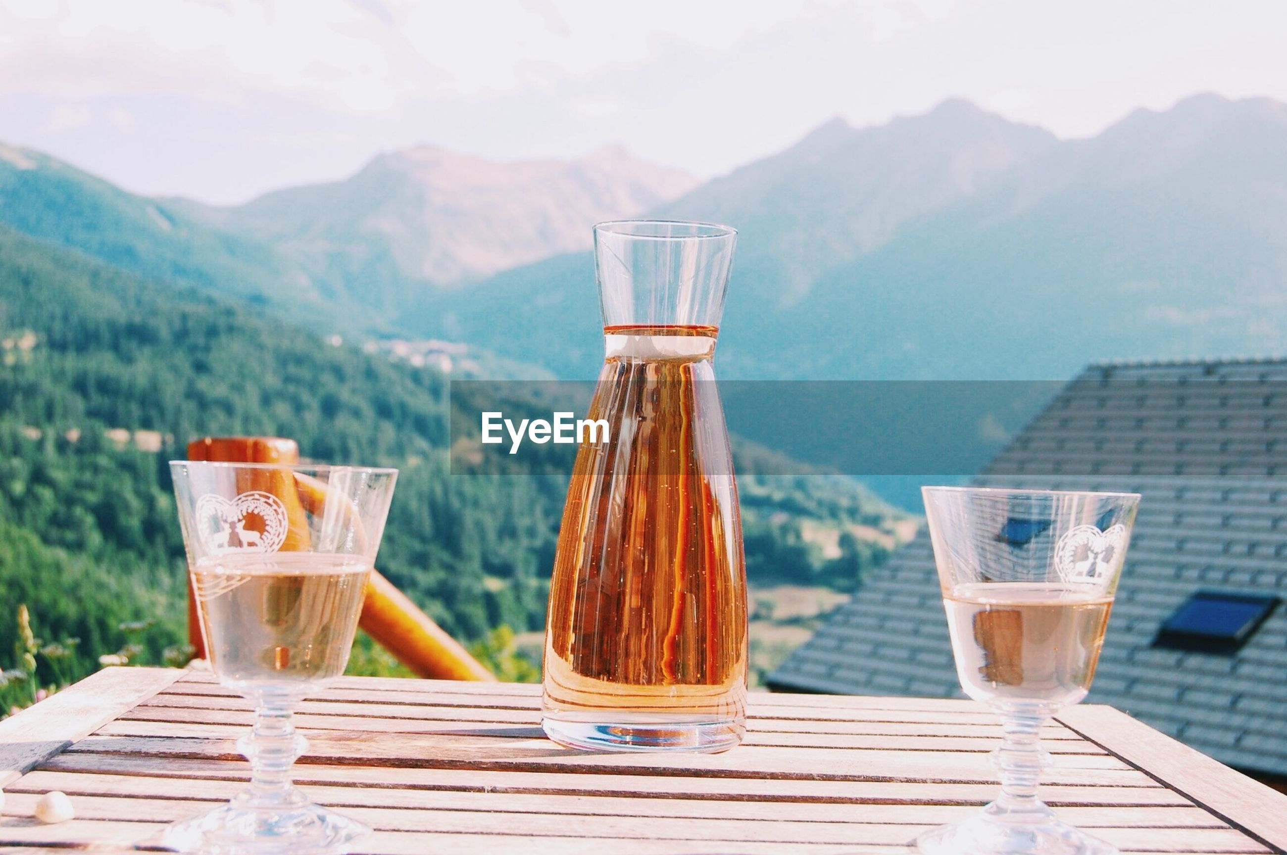 mountain, food and drink, table, drink, refreshment, freshness, wood - material, mountain range, sky, tranquil scene, landscape, day, still life, drinking glass, wooden, absence, tranquility, outdoors, empty, no people