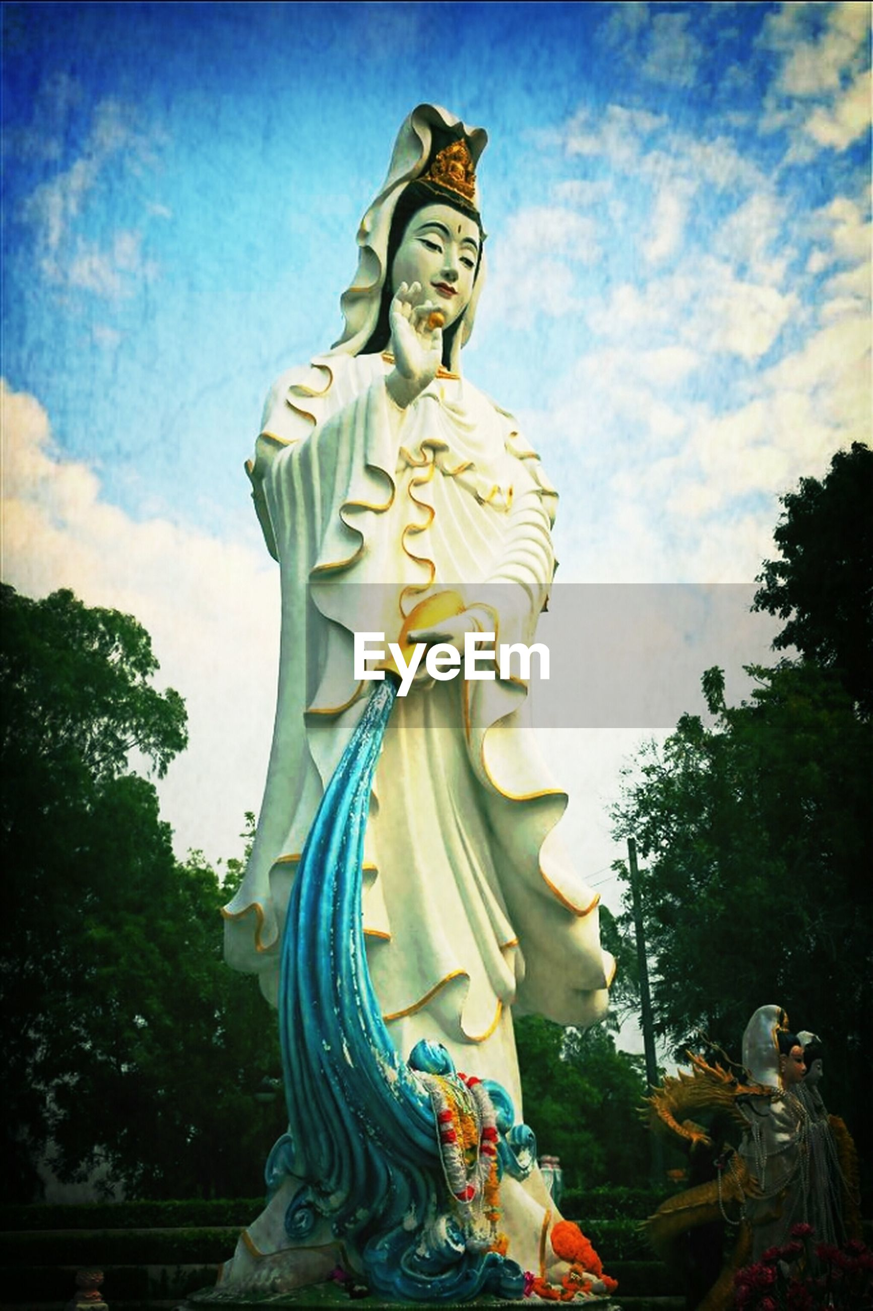 Low angle view of female statue against cloudy sky