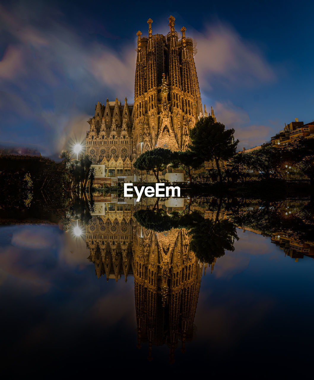 A frontal view of sagrada familia's nativity facade at night and it's reflection in a nearby pond