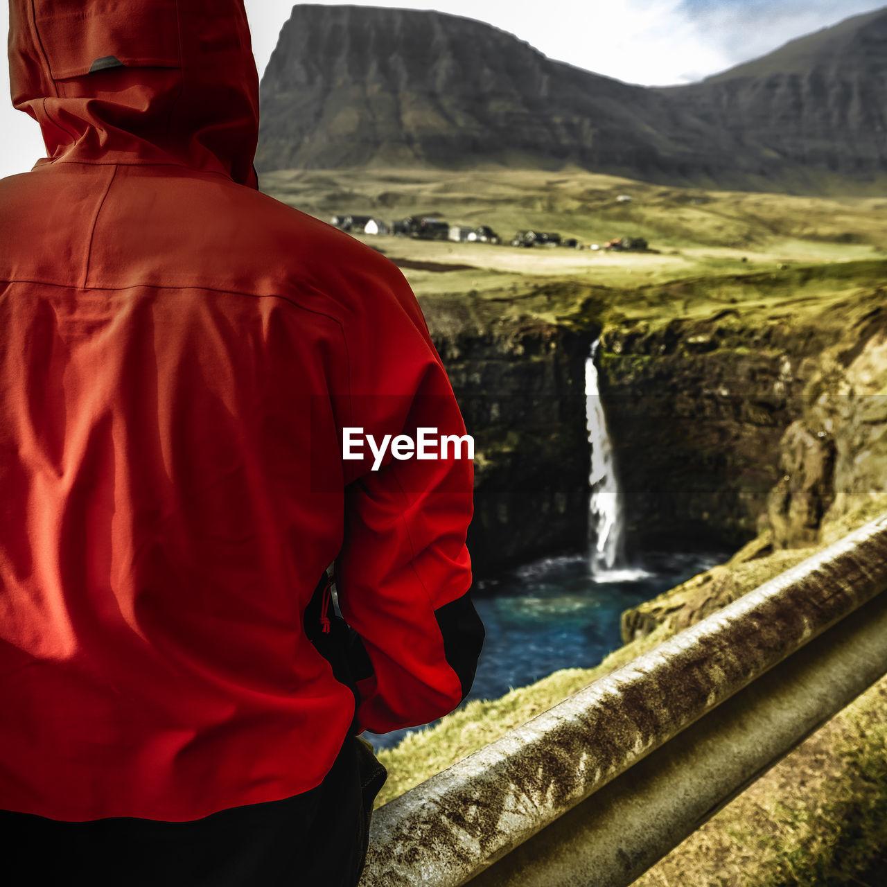 Solo traveller looking towards mulafossur waterfall in the faroe islands