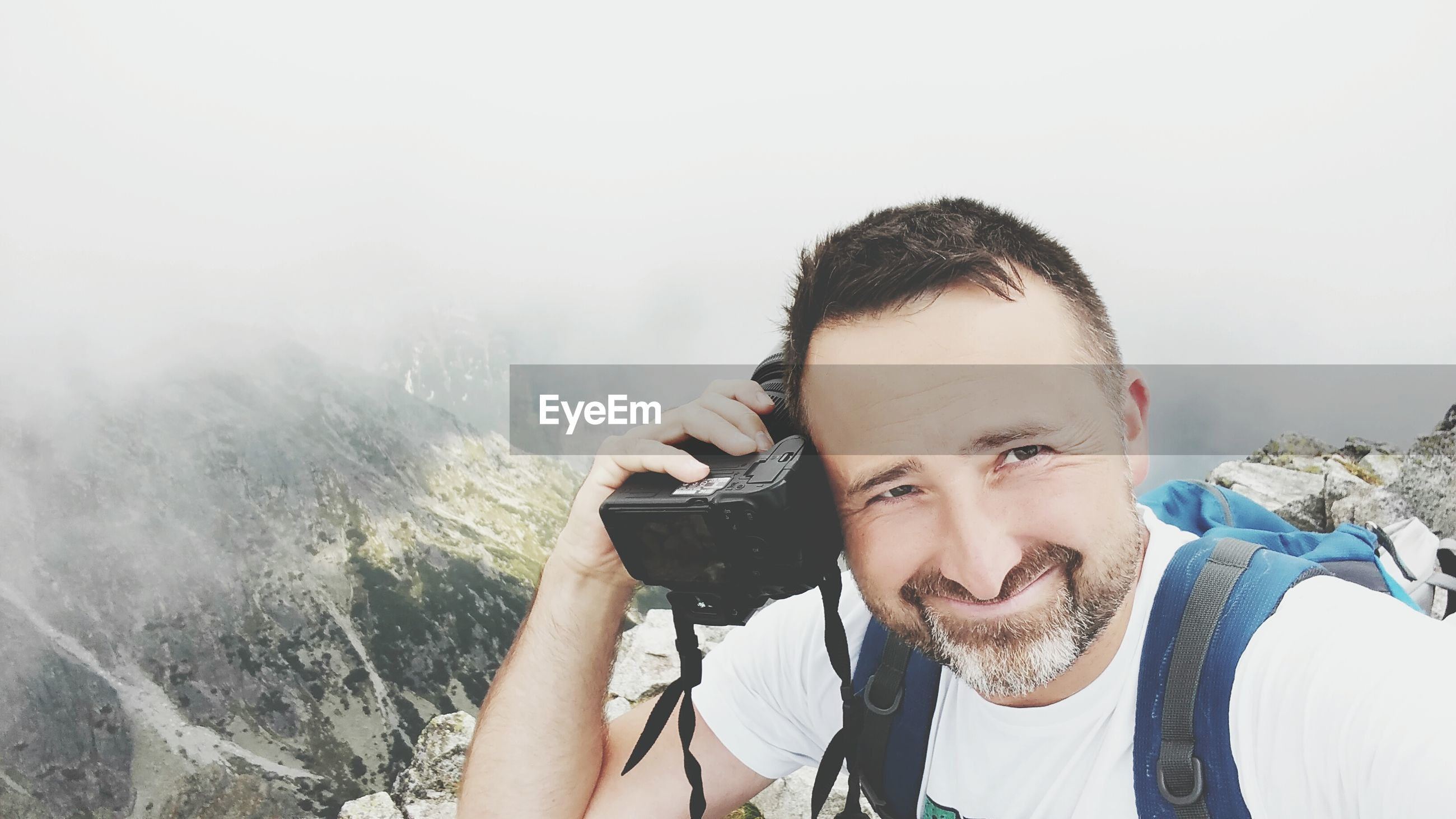 High angle portrait of smiling man holding camera on mountain in foggy weather