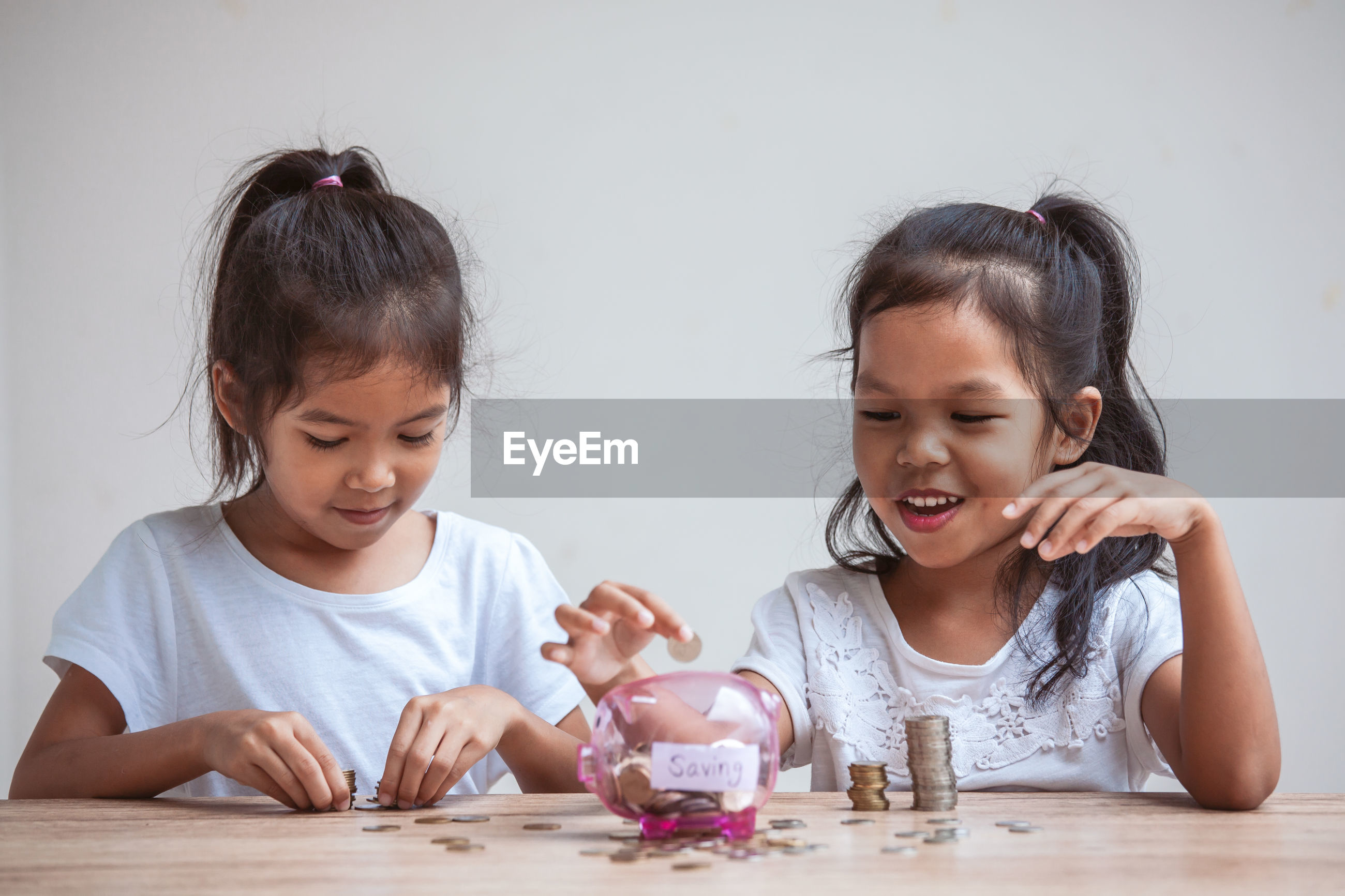 Sisters inserting coins in piggy bank on table against wall