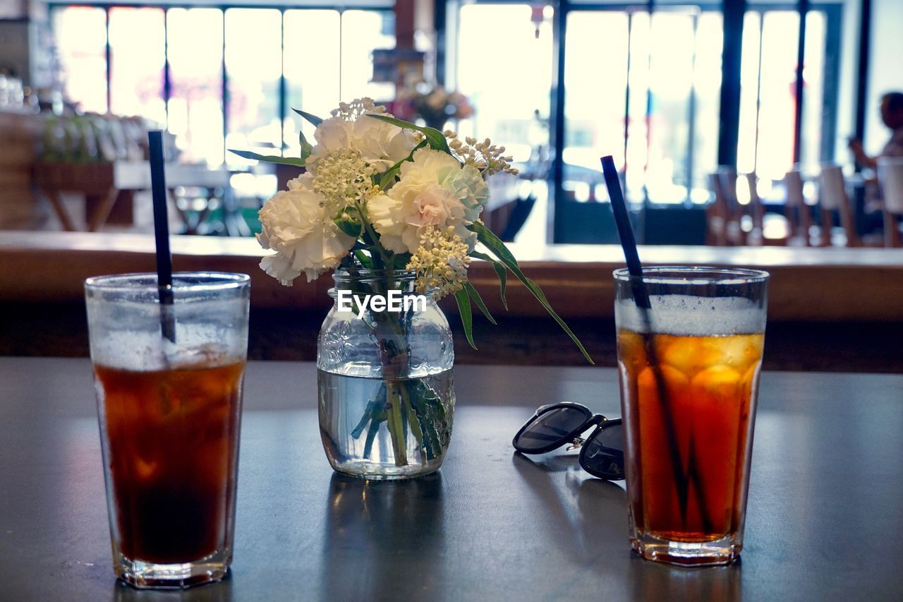 drink, refreshment, food and drink, glass, table, alcohol, drinking glass, freshness, household equipment, focus on foreground, indoors, glass - material, bar - drink establishment, close-up, transparent, still life, no people, restaurant, flower, flowering plant, bar counter