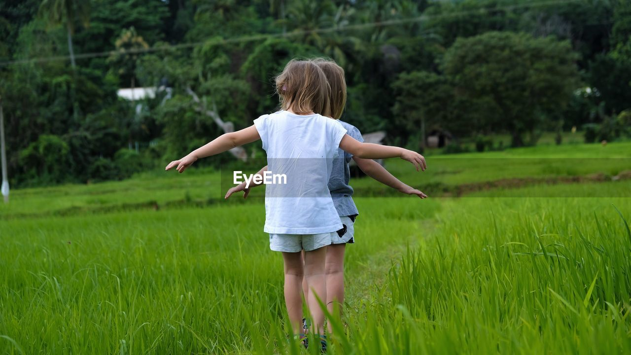Rear view of girls standing by plants on field