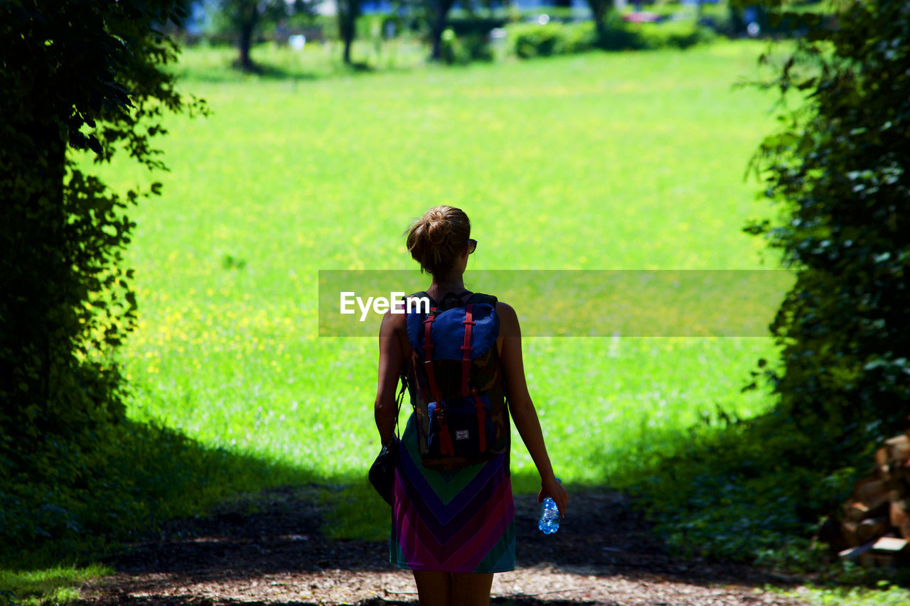 Rear view of woman with backpack standing on field