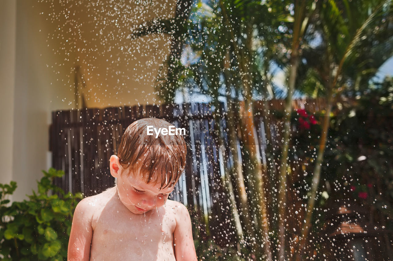 Cute little boy with blonde hair standing under the jets of water.