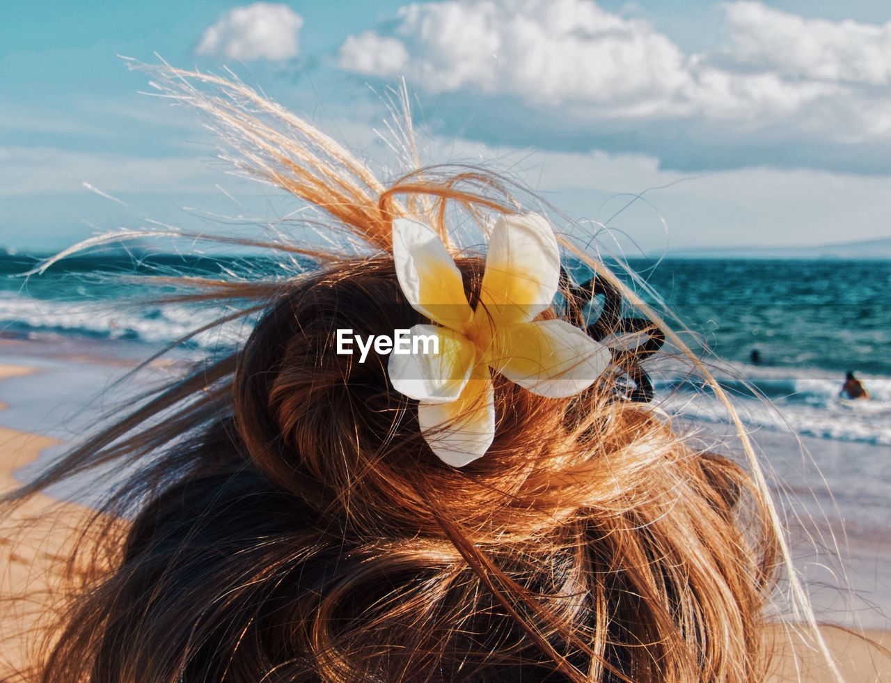 Rear view of woman wearing flower at beach against sky