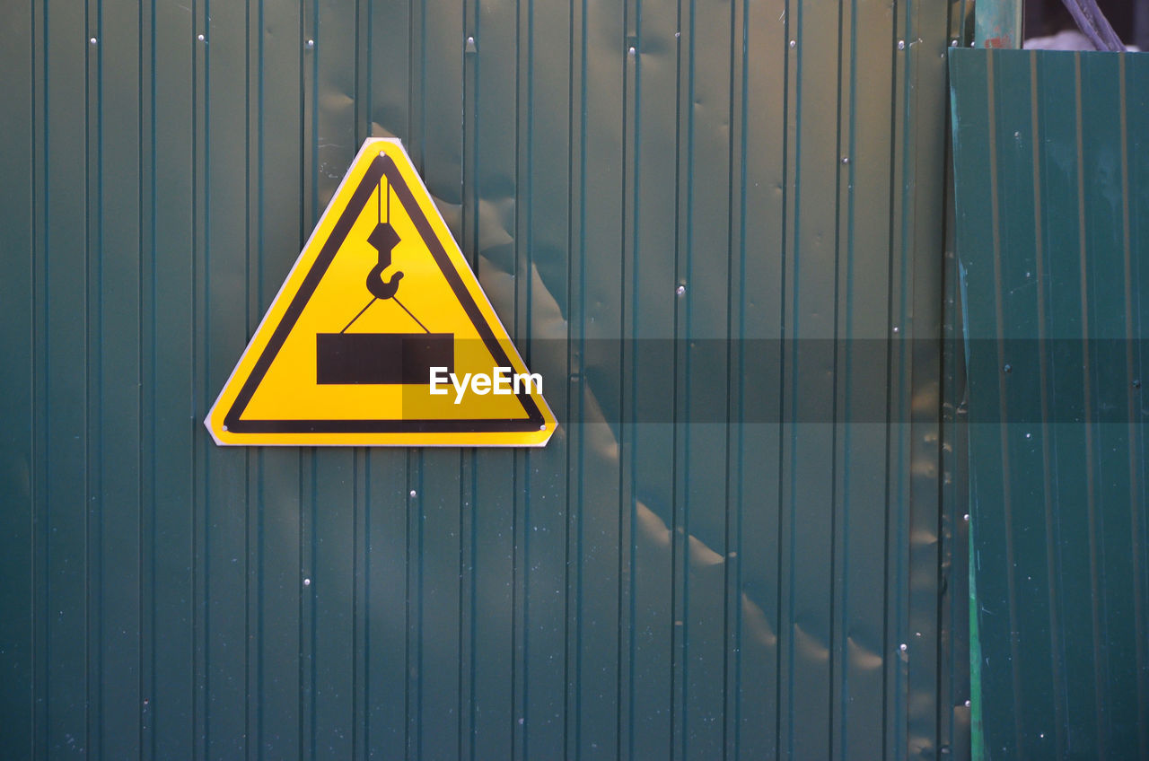 sign, communication, yellow, warning sign, safety, information sign, triangle shape, information, high voltage sign, protection, shape, electricity, warning symbol, security, wall - building feature, day, no people, metal, outdoors, pattern