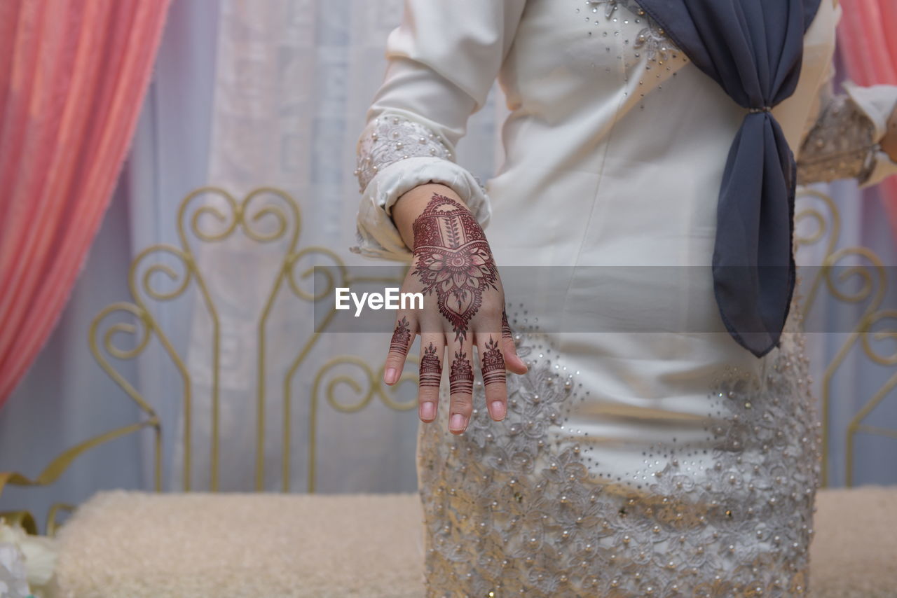 real people, midsection, one person, traditional clothing, wedding, indoors, lifestyles, bride, women, standing, wedding dress, day, life events, men, human hand, close-up, bridegroom, people