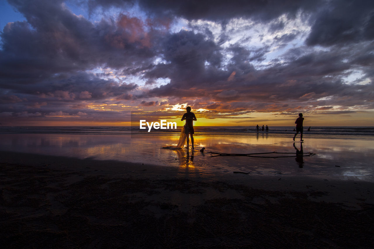 Men Standing On Beach Against Cloudy Sky During Sunset
