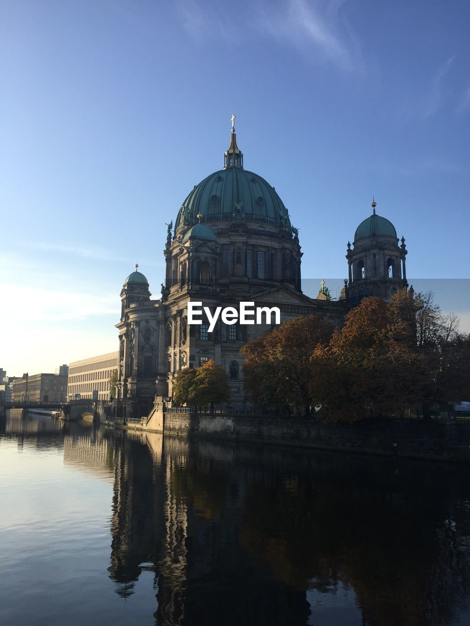 Berlin cathedral by river against blue sky