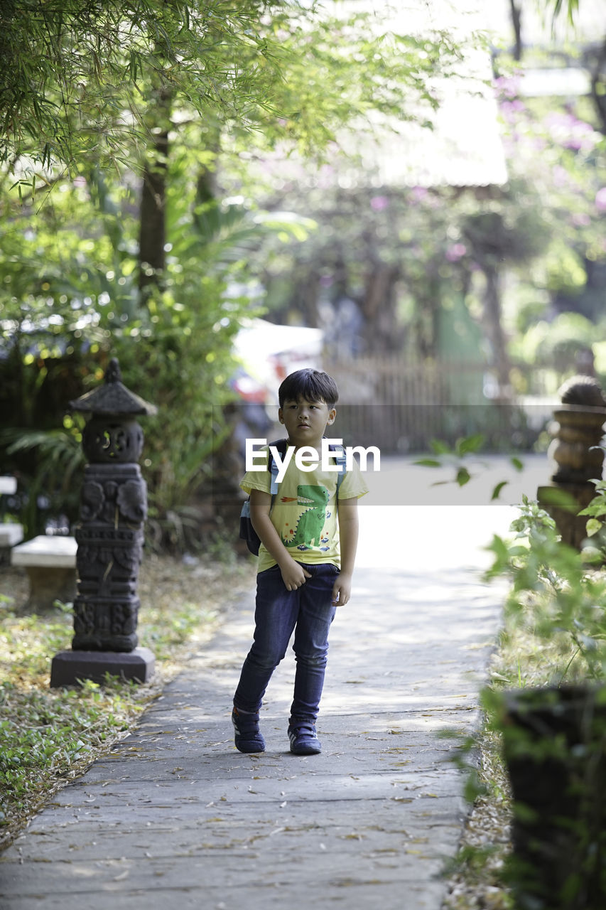full length, casual clothing, real people, plant, one person, child, tree, childhood, day, boys, males, leisure activity, lifestyles, front view, focus on foreground, footpath, nature, standing, outdoors, innocence, teenager