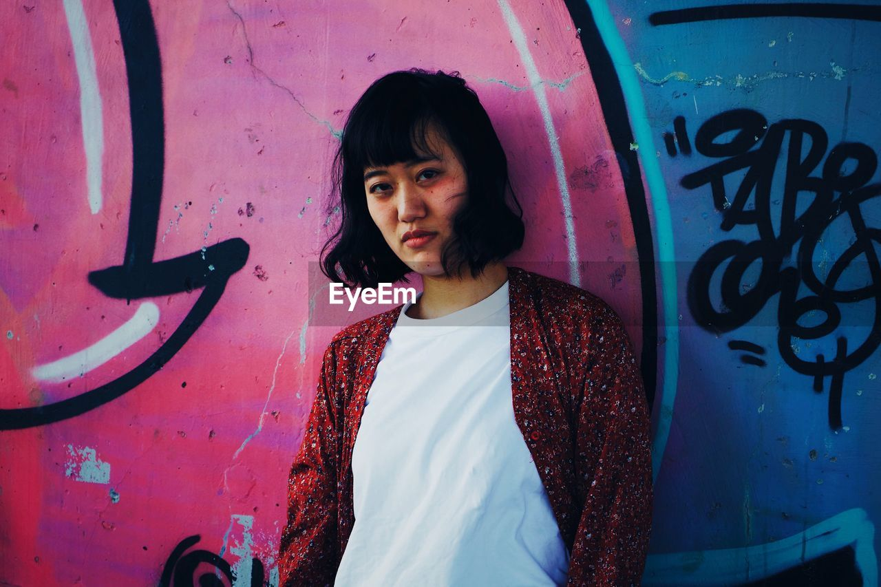 one person, standing, real people, lifestyles, graffiti, wall - building feature, leisure activity, front view, casual clothing, looking at camera, young adult, portrait, waist up, black hair, women, three quarter length, young women, hairstyle