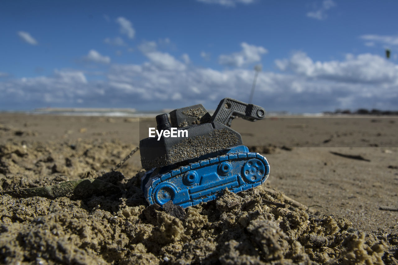 land, sky, toy, cloud - sky, day, sand, no people, nature, blue, selective focus, close-up, focus on foreground, still life, landscape, outdoors, sunlight, toy car, rock, tranquility, arid climate