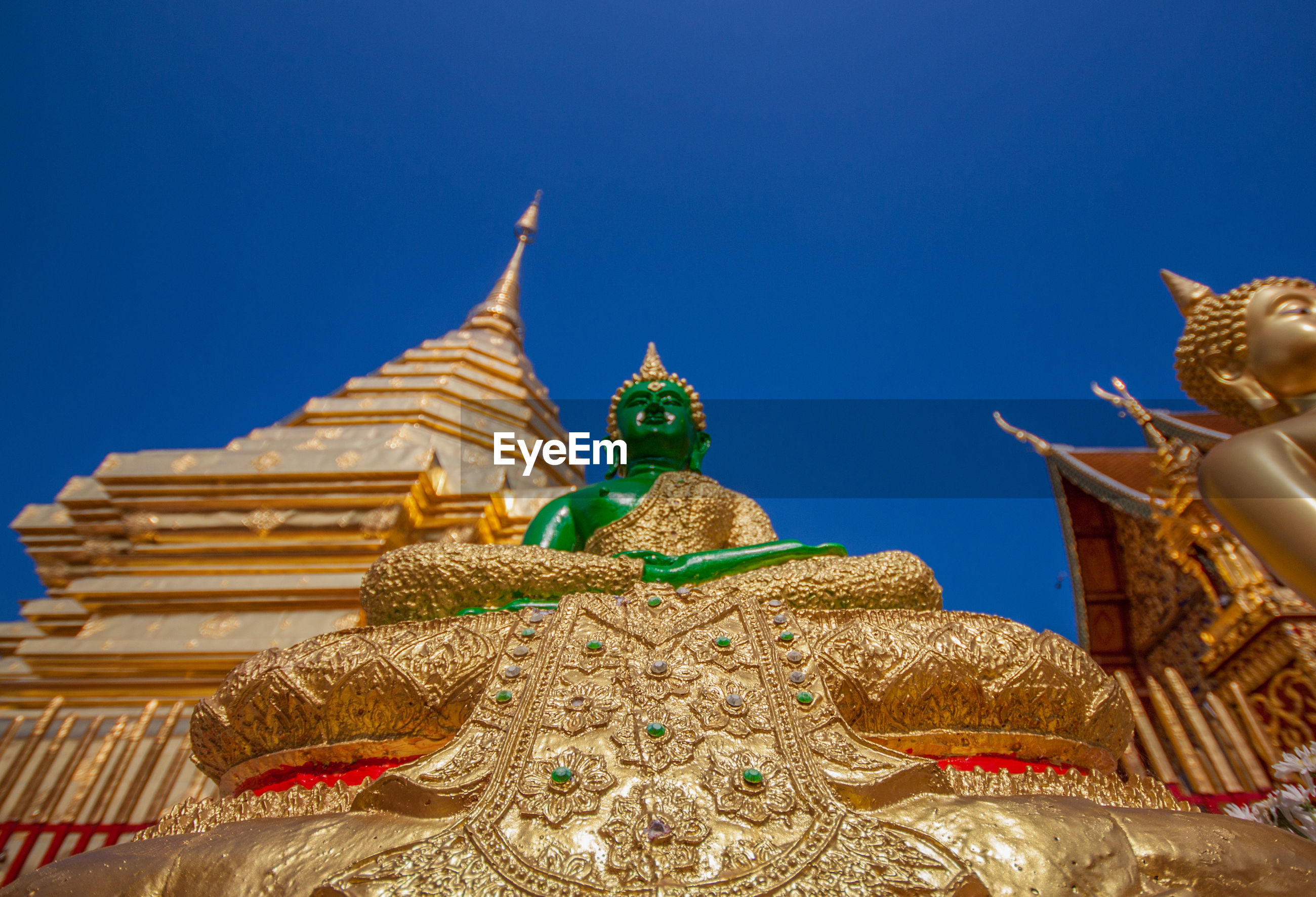 Low angle view of buddha statue by temple against clear blue sky during sunny day