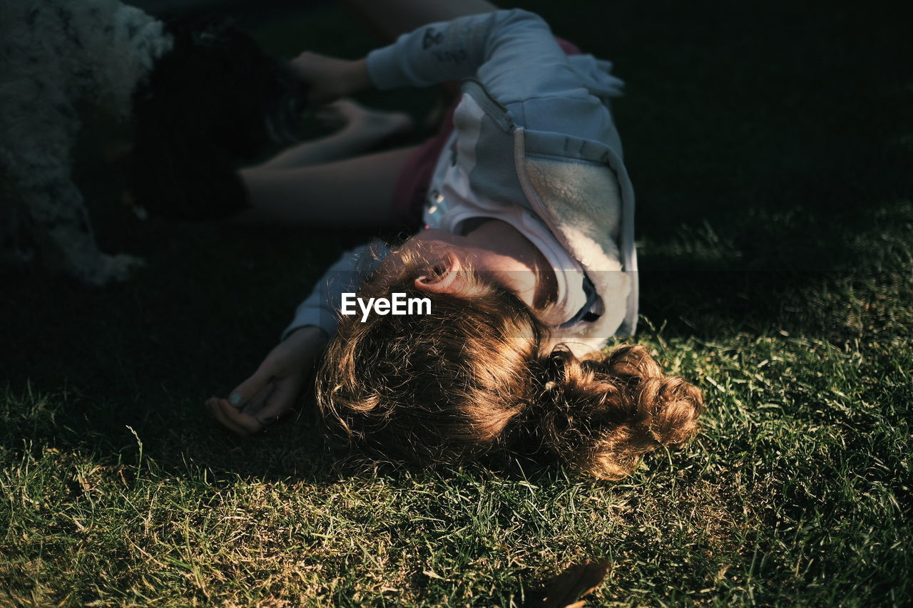 High Angle View Of Girl Lying On Field