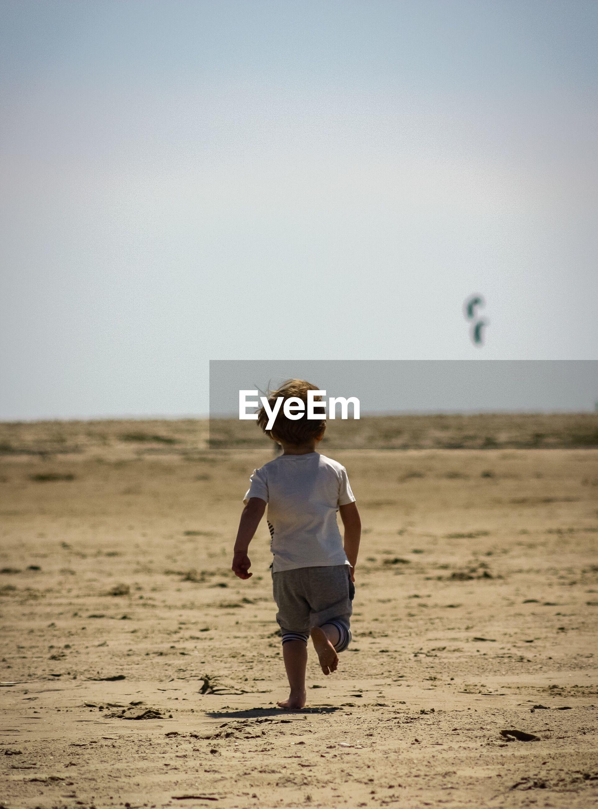 Rear view of boy walking on sand