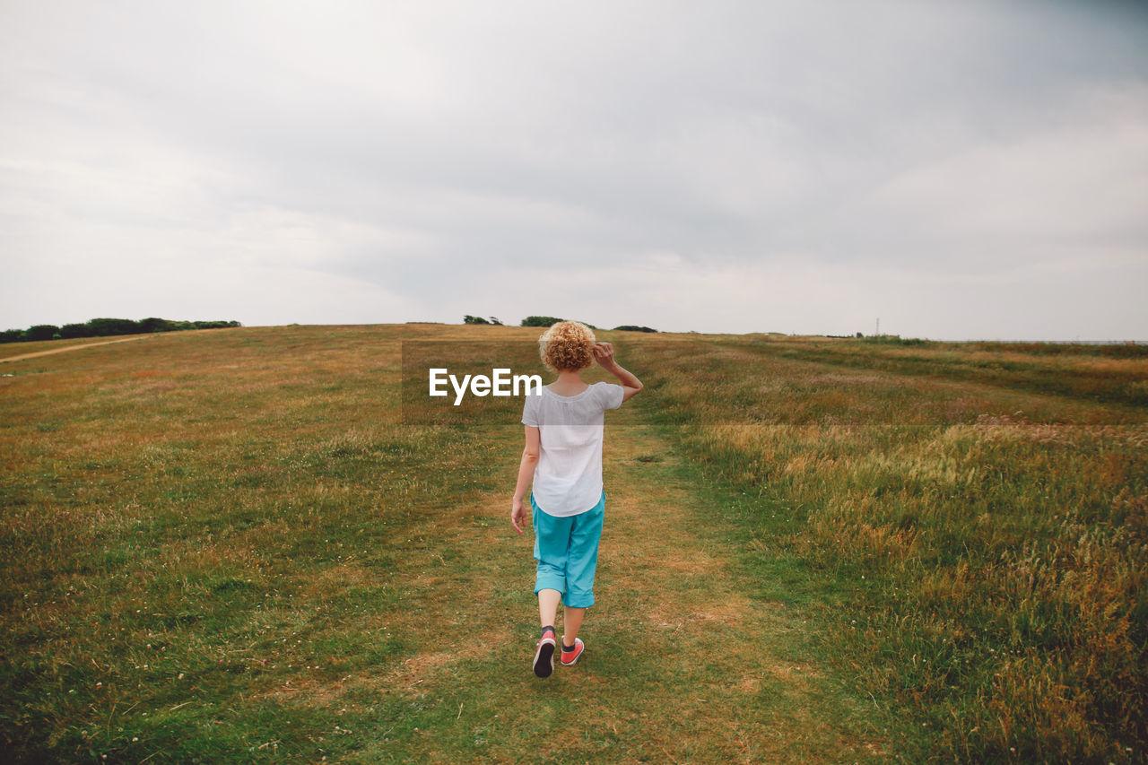 Rear View Of Woman Walking On Grassy Landscape Against Sky