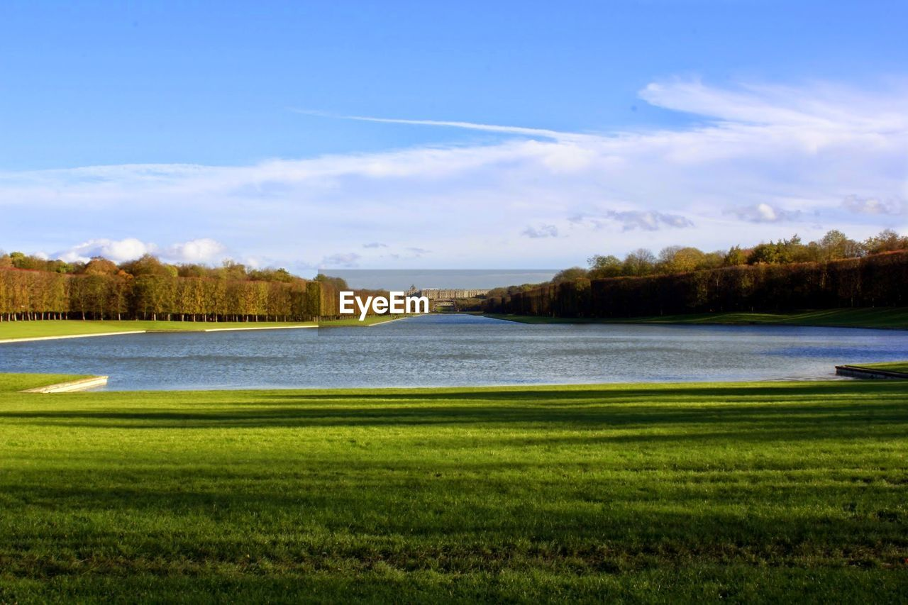 River And Grassy Field Against Cloudy Sky On Sunny Day