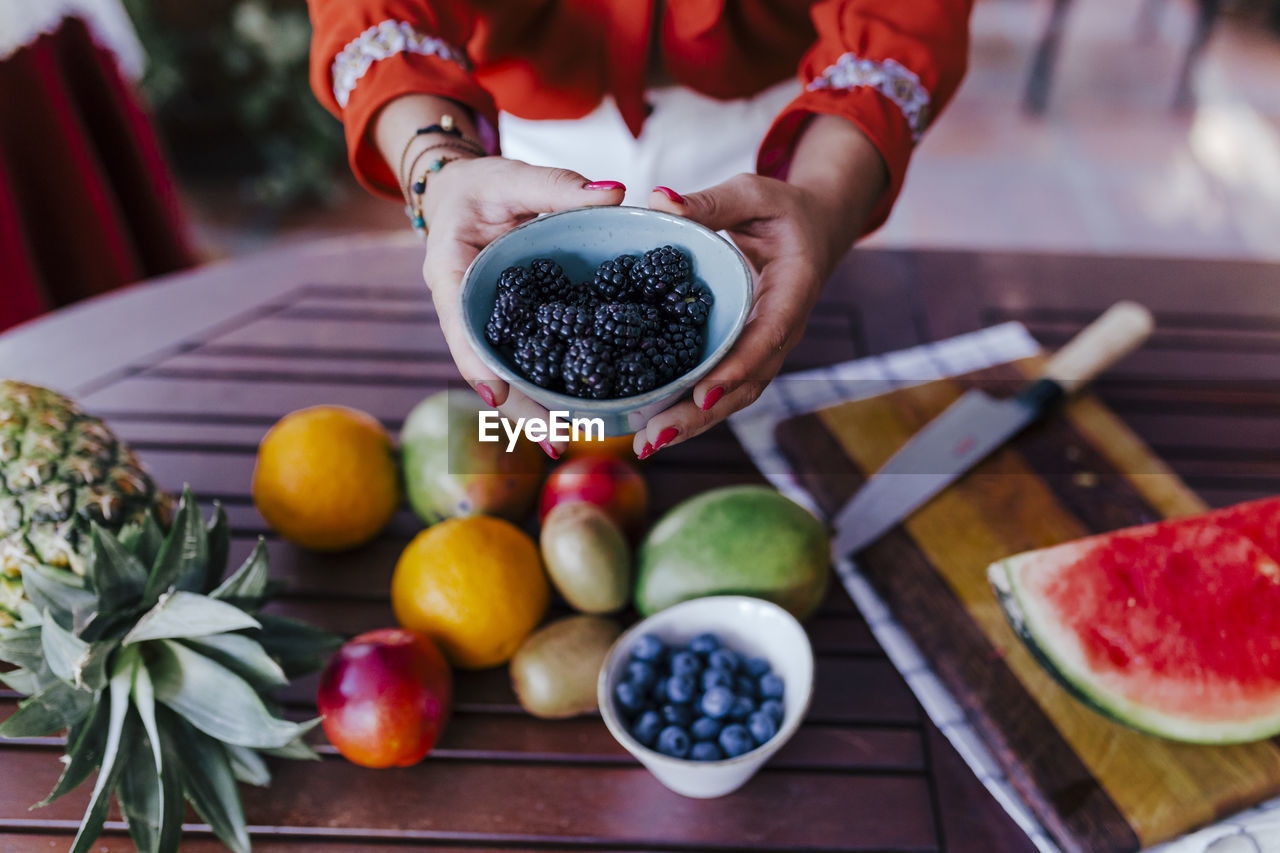 fruit, food and drink, healthy eating, food, freshness, wellbeing, one person, table, real people, human hand, holding, hand, focus on foreground, lifestyles, berry fruit, human body part, adult, midsection, women, preparation, orange
