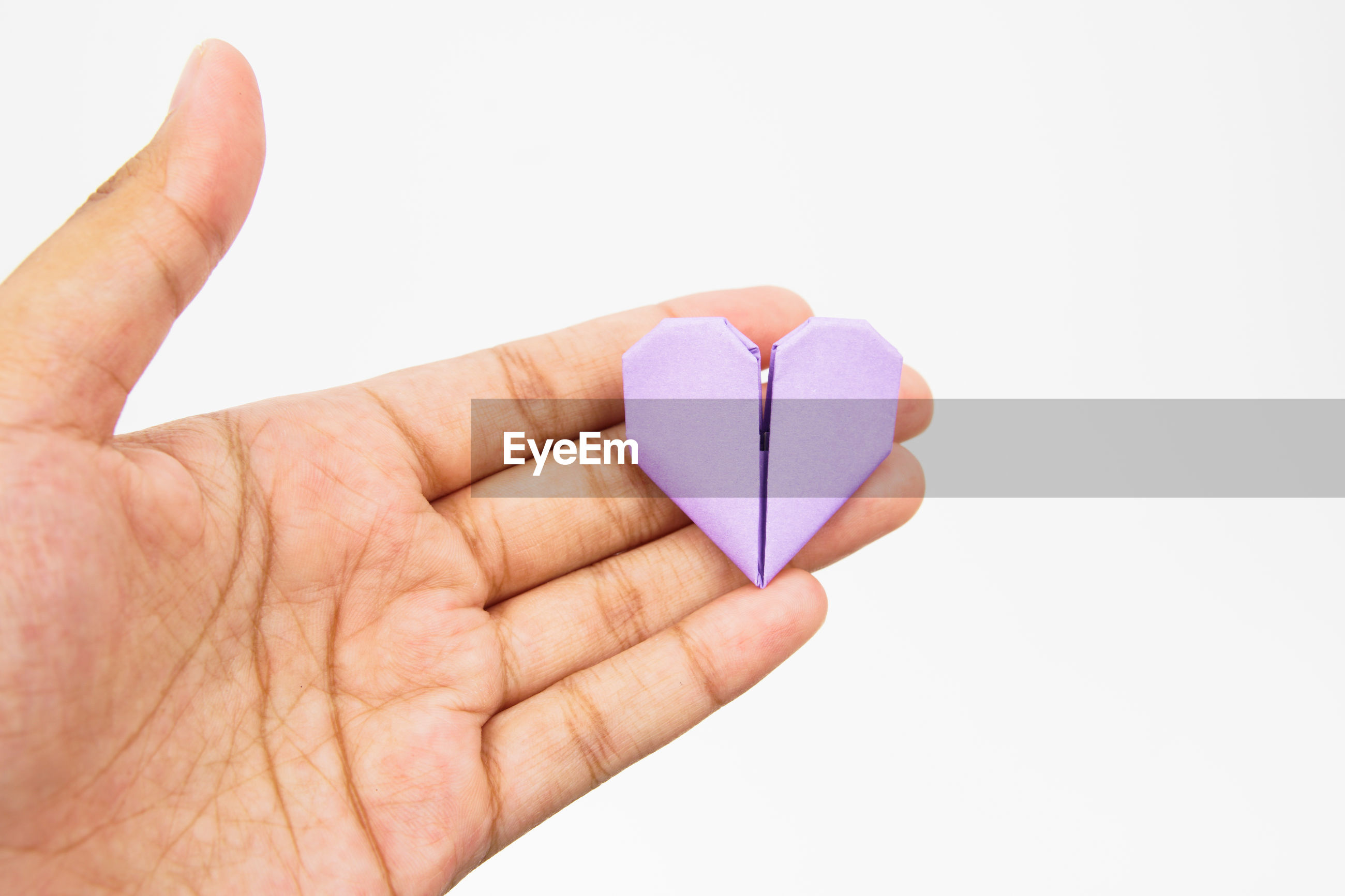 Close-up of cropped hand holding heart shape purple papers against white background