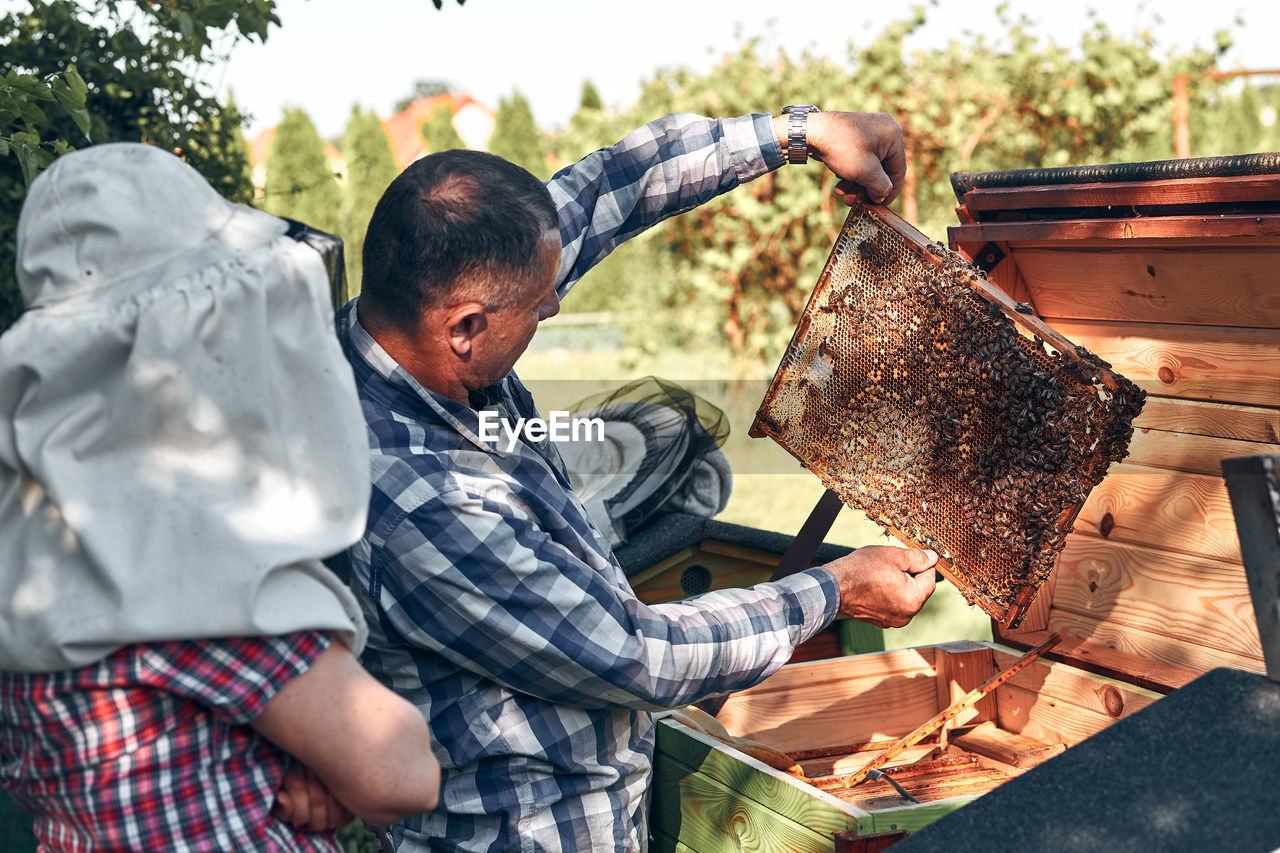 Person standing by bee keeper working in park