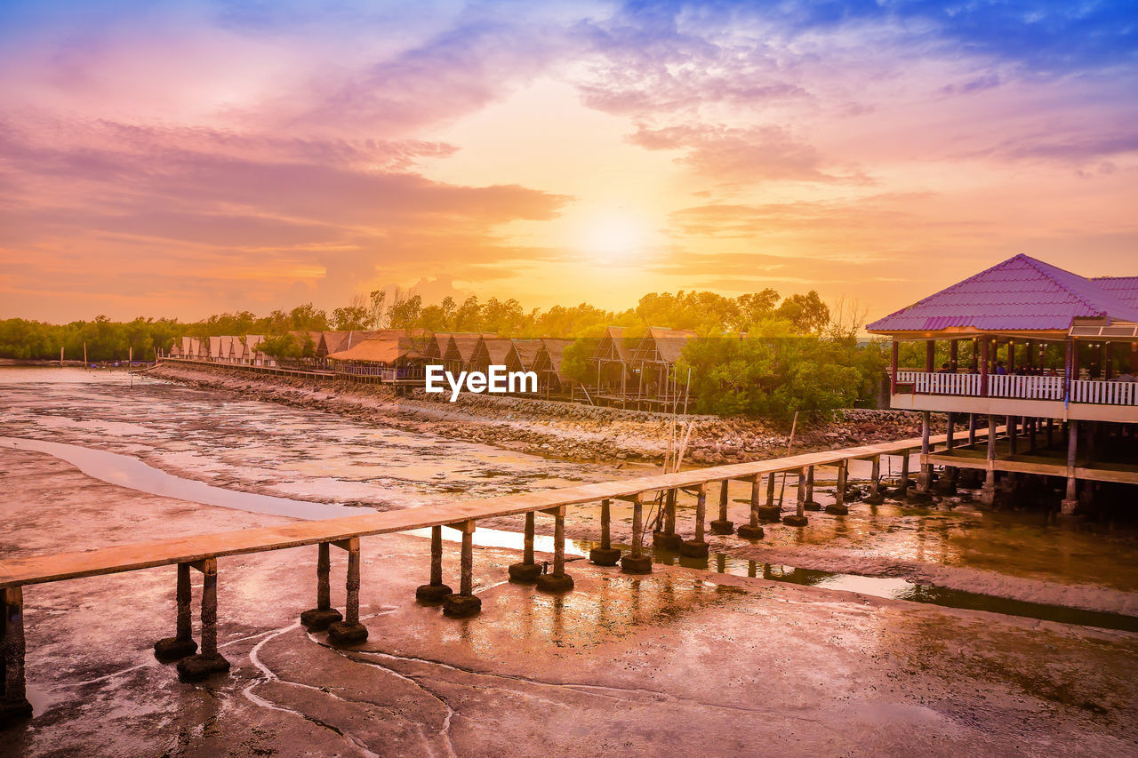sky, architecture, built structure, sunset, orange color, water, cloud - sky, beauty in nature, nature, no people, building exterior, land, tree, building, tranquility, scenics - nature, sun, railing, wood - material